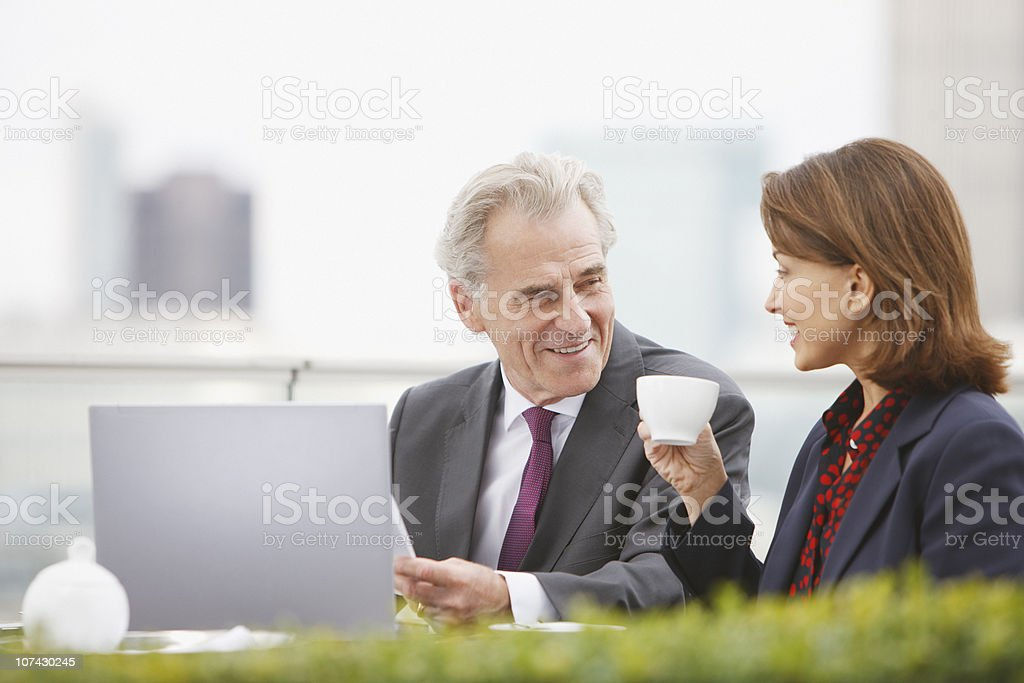 Business people drinking coffee and working outdoors royalty-free stock photo