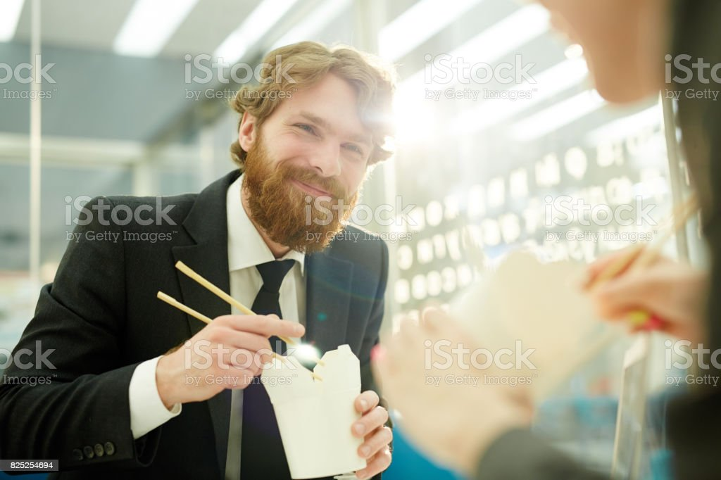 Portrait of modern bearded businessman smiling happily while eating...