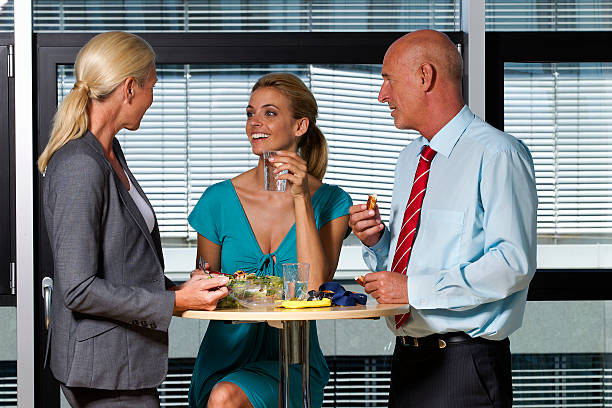 geschäftsleute essen mittagessen im büro - arbeit in münchen stock-fotos und bilder
