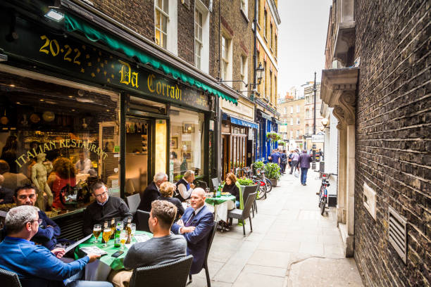 Business people eating lunch outdoors in Mayfair, central London, UK London, UK - May 18, 2017: businessmen enjoy an al fresco lunch at an Italian restaurant in Mayfair, an exclusive, wealthy area in central London, UK. The men are drinking beers and looking at the menu. The street is narrow and quaint, emphasising the diminishing perspective of the image. Horizontal colour image with copy space. mayfair stock pictures, royalty-free photos & images
