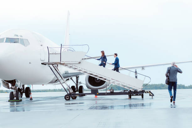 Business people entering the airplane stock photo