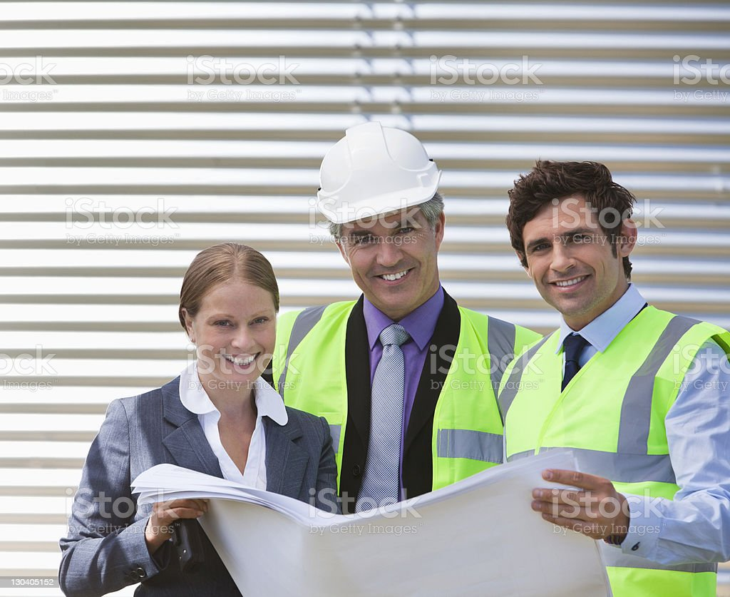 Business people examining blueprints on site royalty-free stock photo