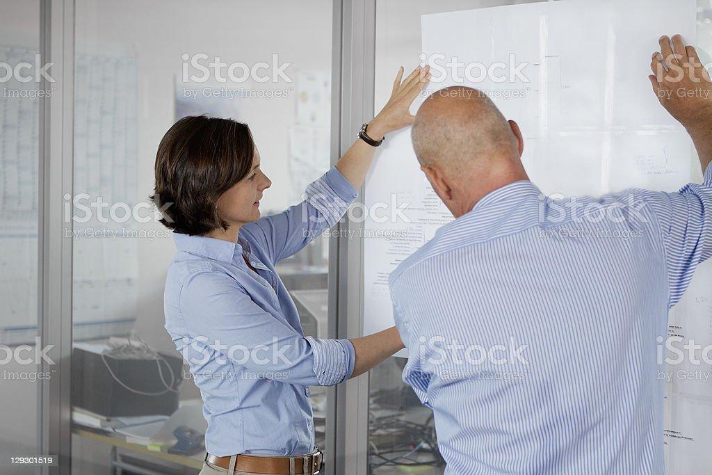 Business people examining blueprints royalty-free stock photo
