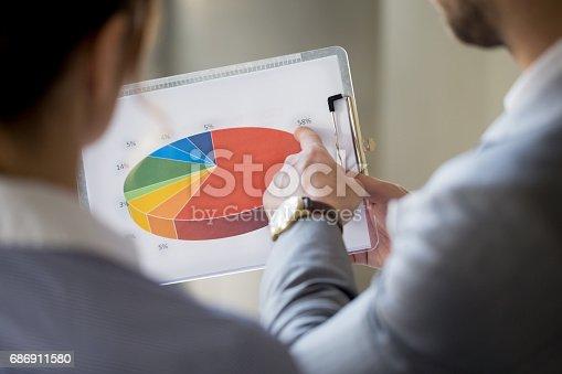 istock Business people examining pie chart 686911580