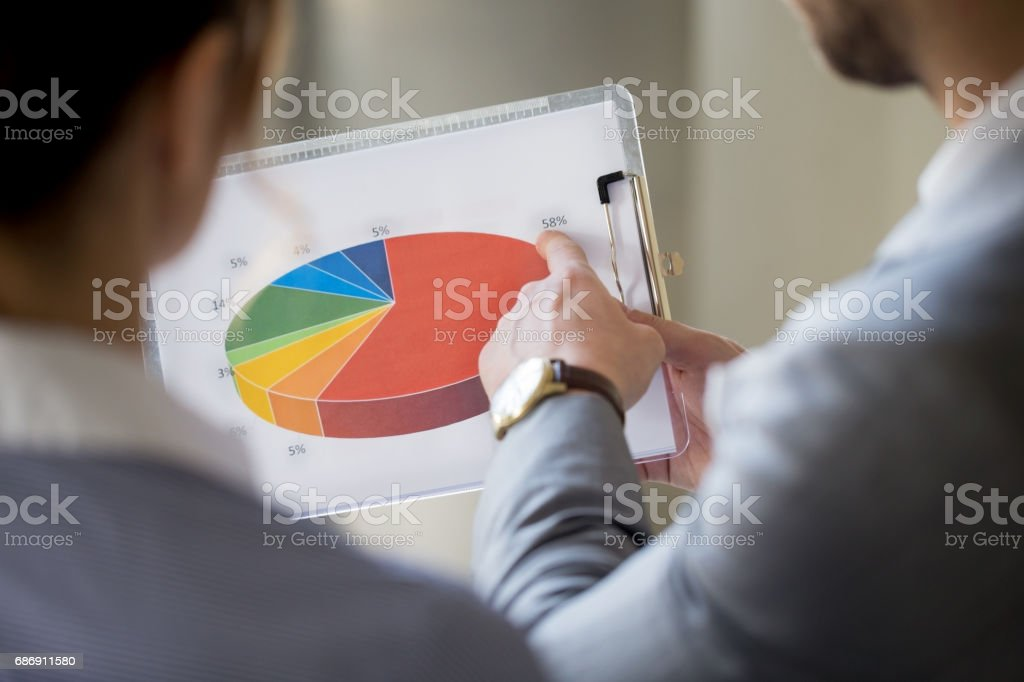 Business people examining pie chart stock photo