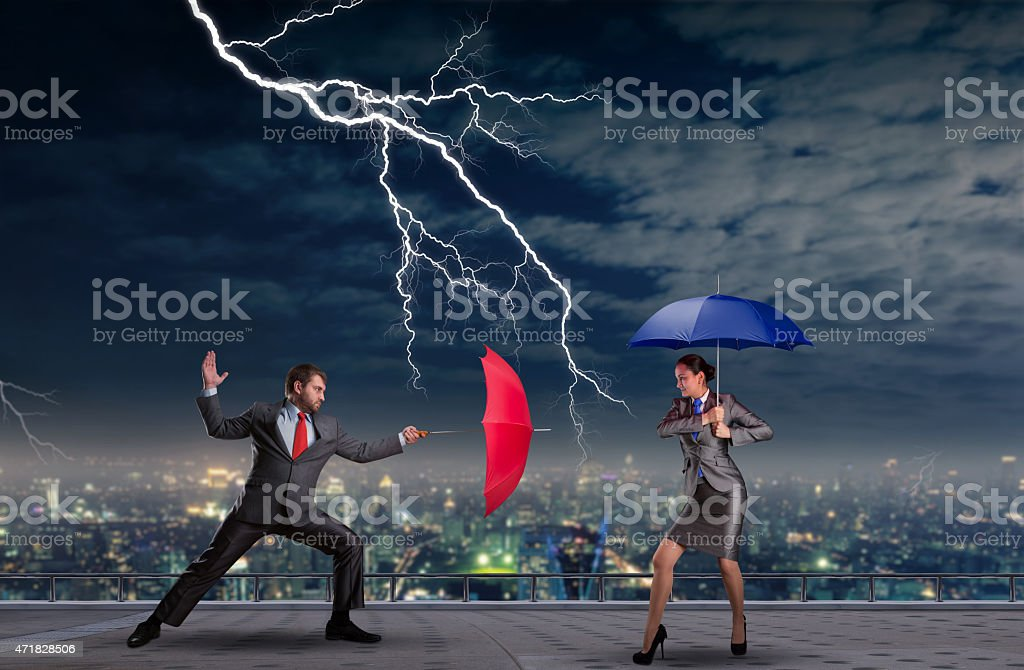 Business people fighting Business people fighting with umbrellas in a thunderstorm 2015 Stock Photo