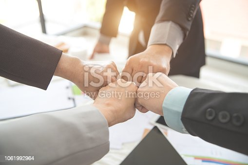 business people giving first bump after completed project during meeting using as background (concept of teamwork and partnership)