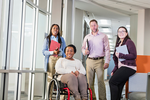 660681964 istock photo Business people going to meeting, woman in wheelchair 1145865646