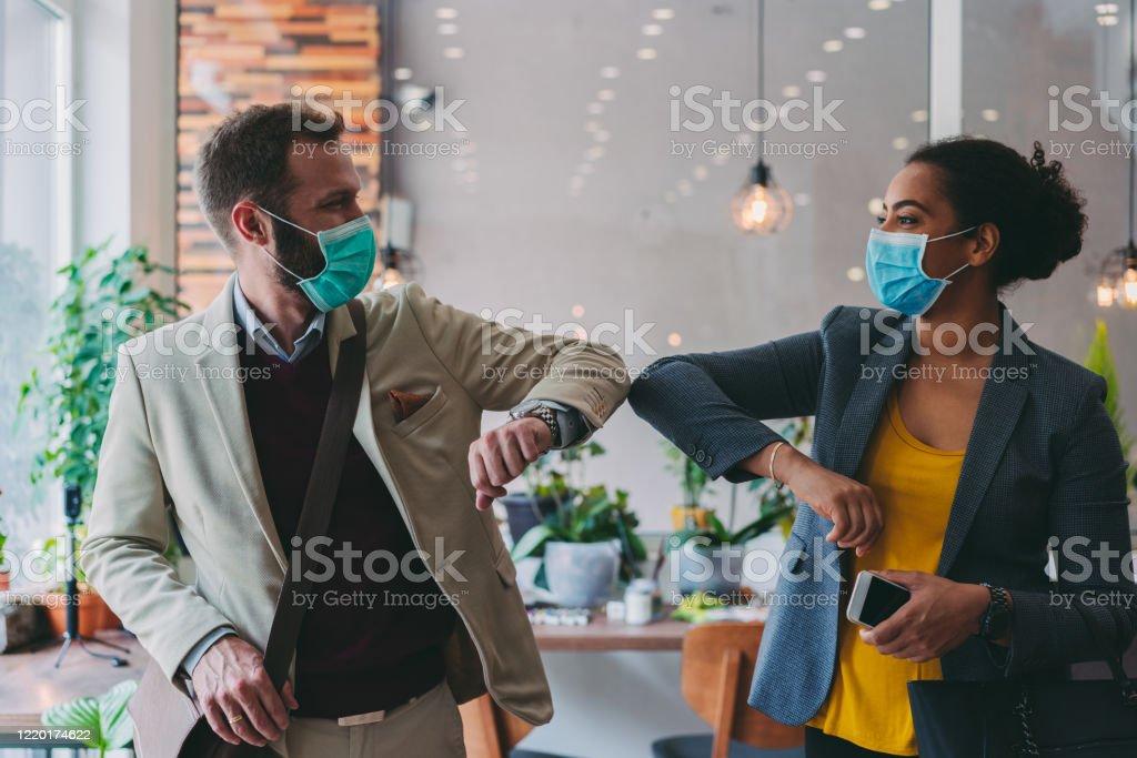 Affärsmän hälsning under COVID-19 pandemi, armbåge bump - Royaltyfri Affärskvinna Bildbanksbilder