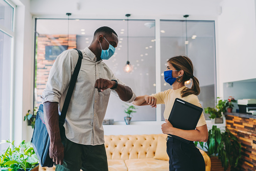 Colleagues in the office practicing alternative greeting to avoid handshakes during COVID-19 pandemic