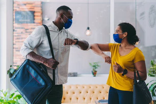 Business people greeting during COVID-19 pandemic, elbow bump stock photo