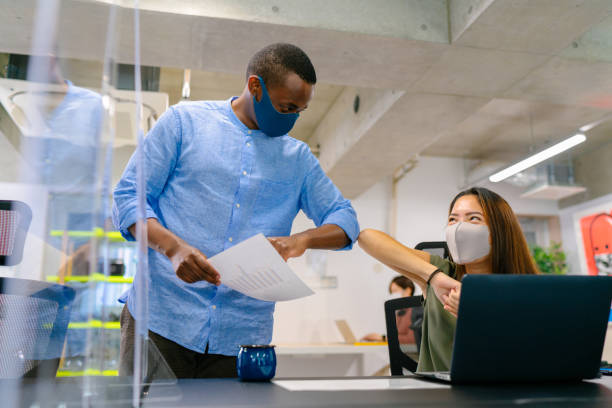 Business people greeting each other with elbow bump in office stock photo