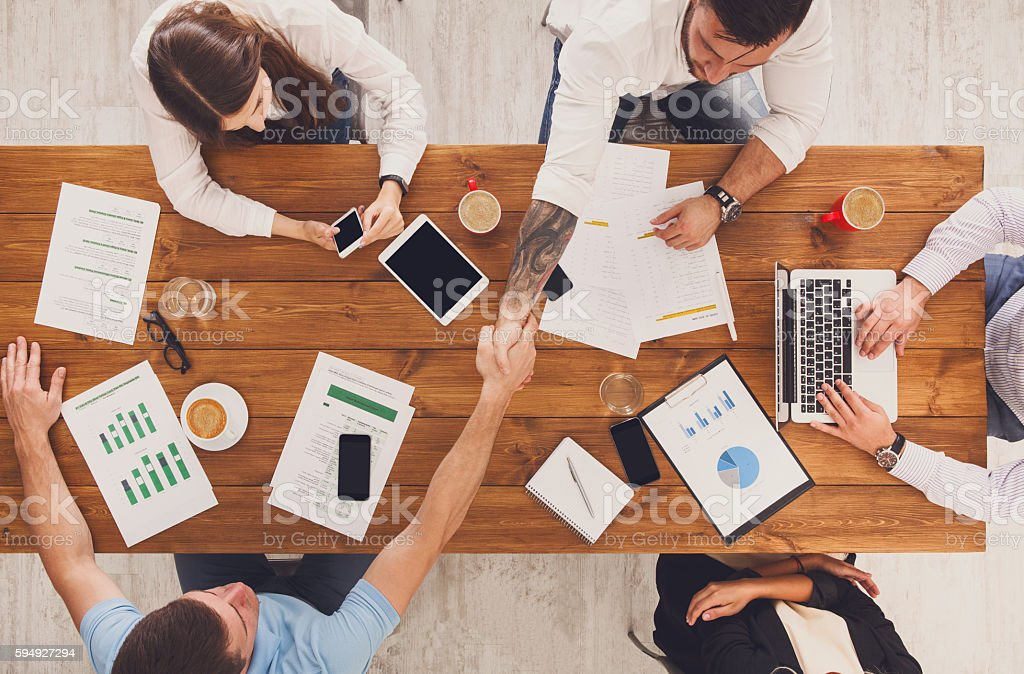 Business meeting. Busy people work in office, top view of wood table...