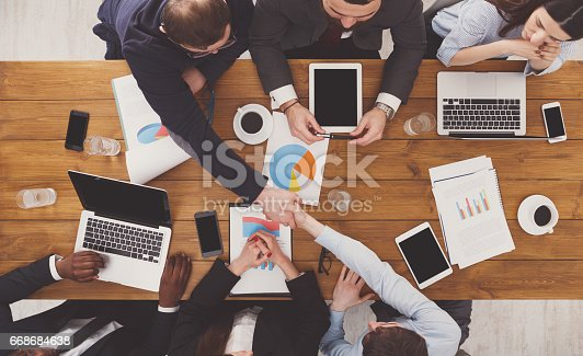 istock Business people group handshake in office, top view 668684638
