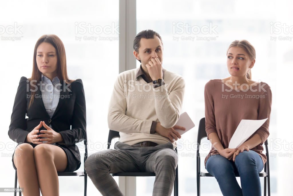 Business people group sitting on chairs waiting, expressing different emotions stock photo