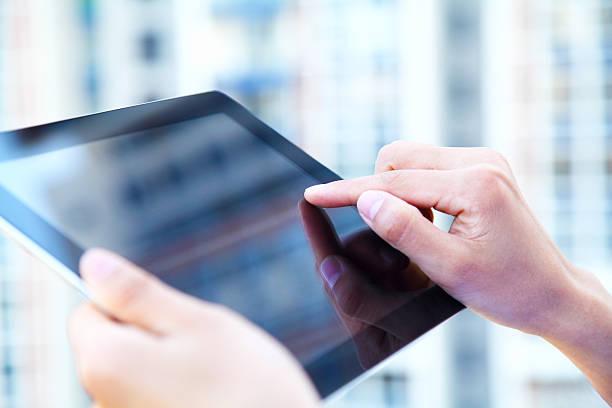 geschäftsleute hand holding digital tablet auf hellblauen hintergrund - blaue kontaktlinsen stock-fotos und bilder