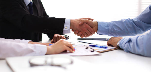 Business people handshake, sitting at the table – zdjęcie