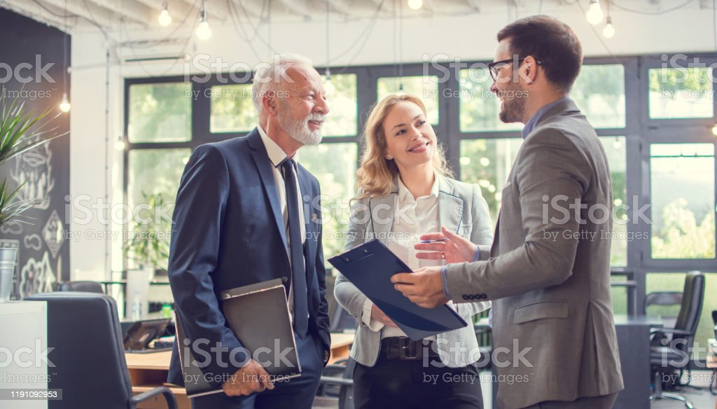Business people having a business meeting. Happy diverse business team young and old workers talking brainstorming on project in office Business people having a business meeting. Happy diverse business team young and old workers talking brainstorming on project in office Active Seniors Stock Photo
