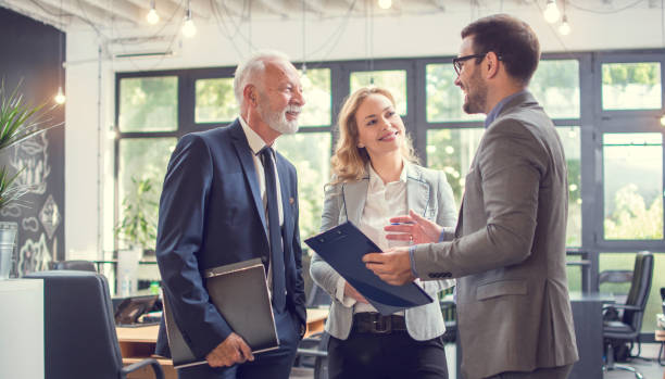 Business people having a business meeting. Happy diverse business team young and old workers talking brainstorming on project in office stock photo