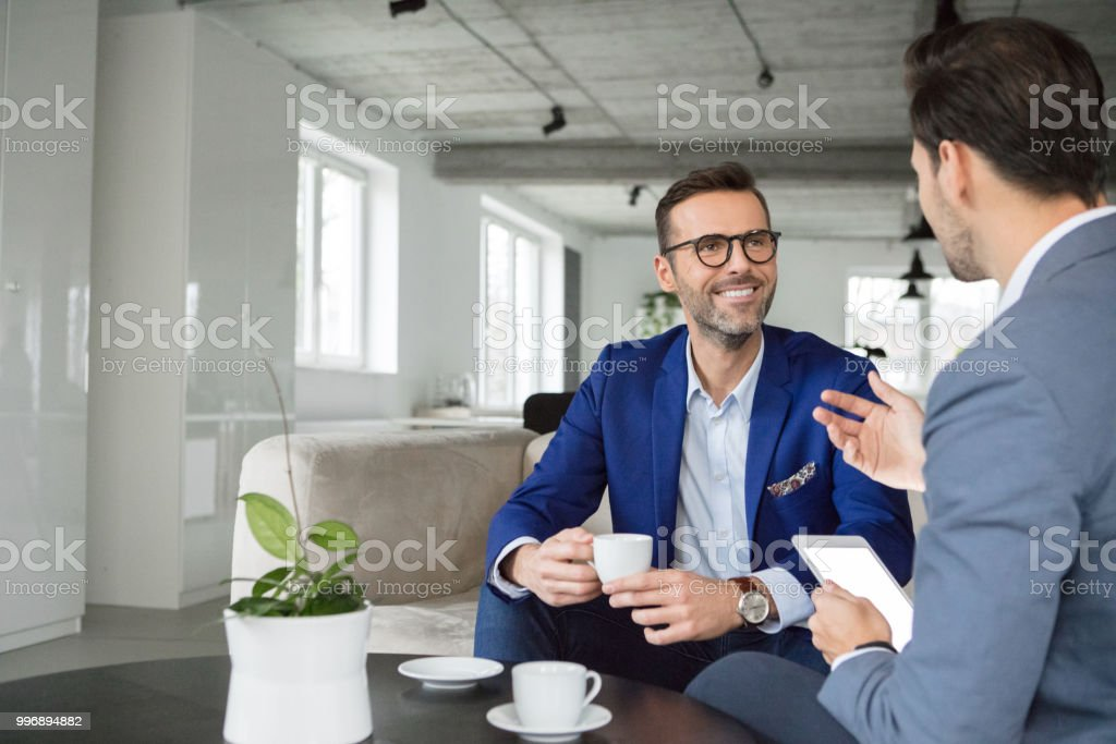 Business people having a discussing in break Mature businessman listening to colleague during coffee break in office Adult Stock Photo
