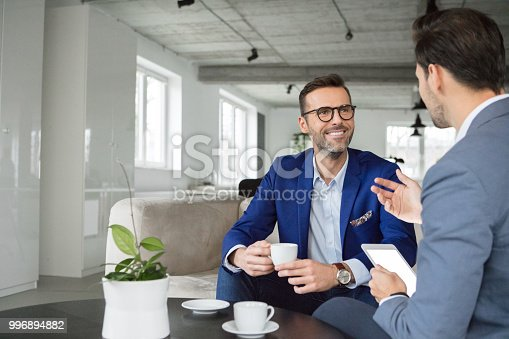 Mature businessman listening to colleague during coffee break in office
