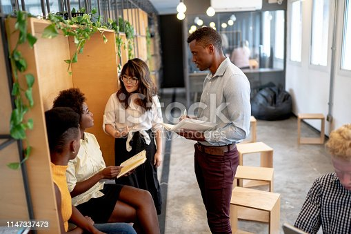 681735120istockphoto Business people having a meeting at modern coworking office 1147337473