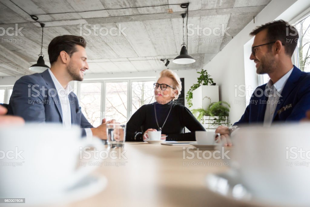 Business people having a productive meeting in office Business people having a productive meeting in office. Group of corporate professionals sitting around conference table and discussing new project. Active Seniors Stock Photo