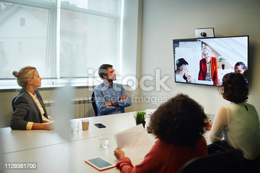 Business People Having a Video Call in Board Room. Sitting by the desk and talking with coworkers on lcd tv.