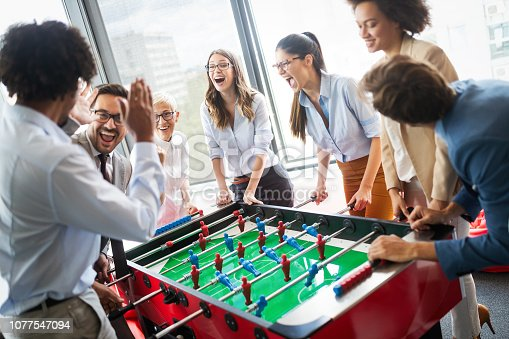 Business people having great time together. Colleagues playing table football in office