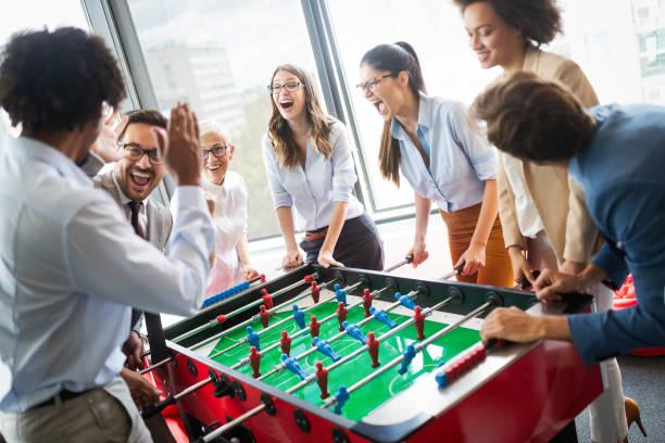 Geschäftsleute, tolle Zeit zusammen. Kolleginnen und Kollegen spielen Tischfussball im modernen Büro – Foto