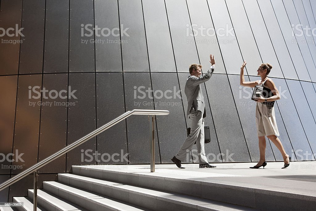 Business people high fiving outdoors royalty-free stock photo