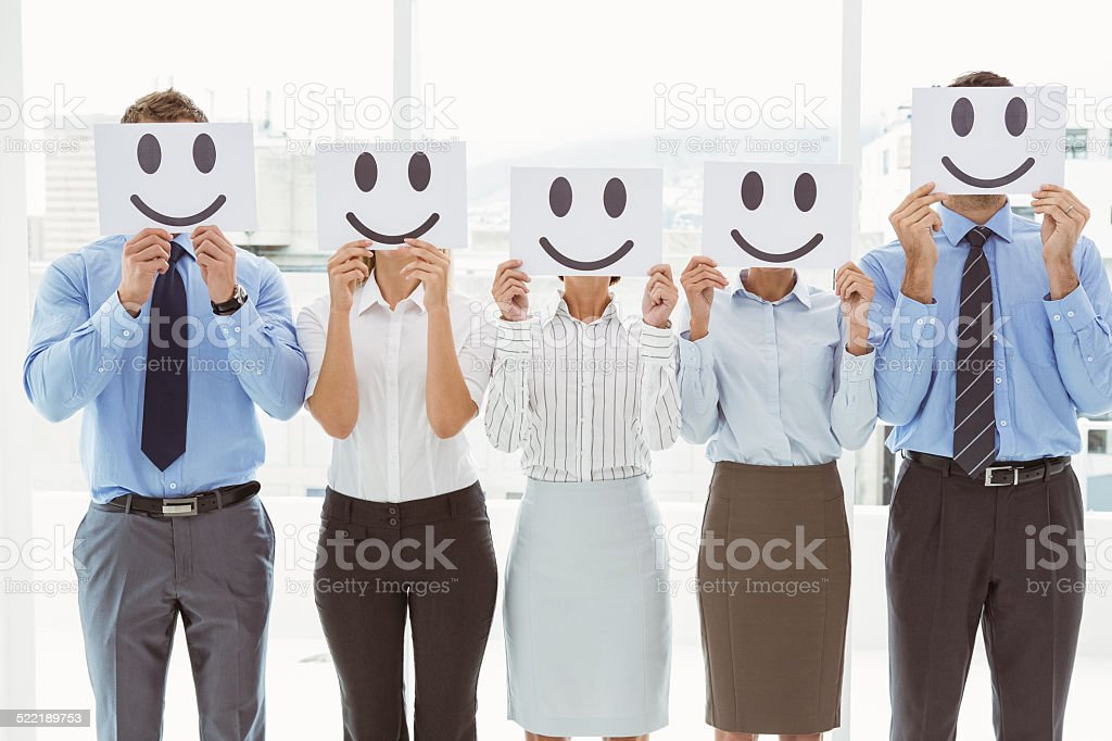 Business people holding happy smileys on faces stock photo