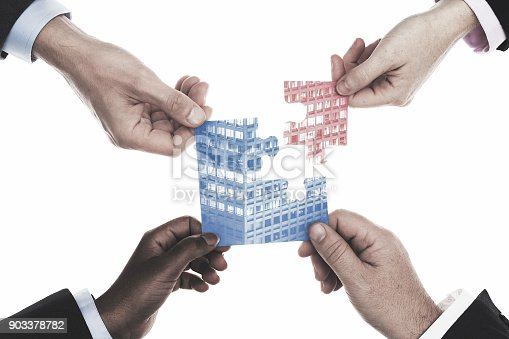 684793898 istock photo Business people holding jigsaw building 903378782