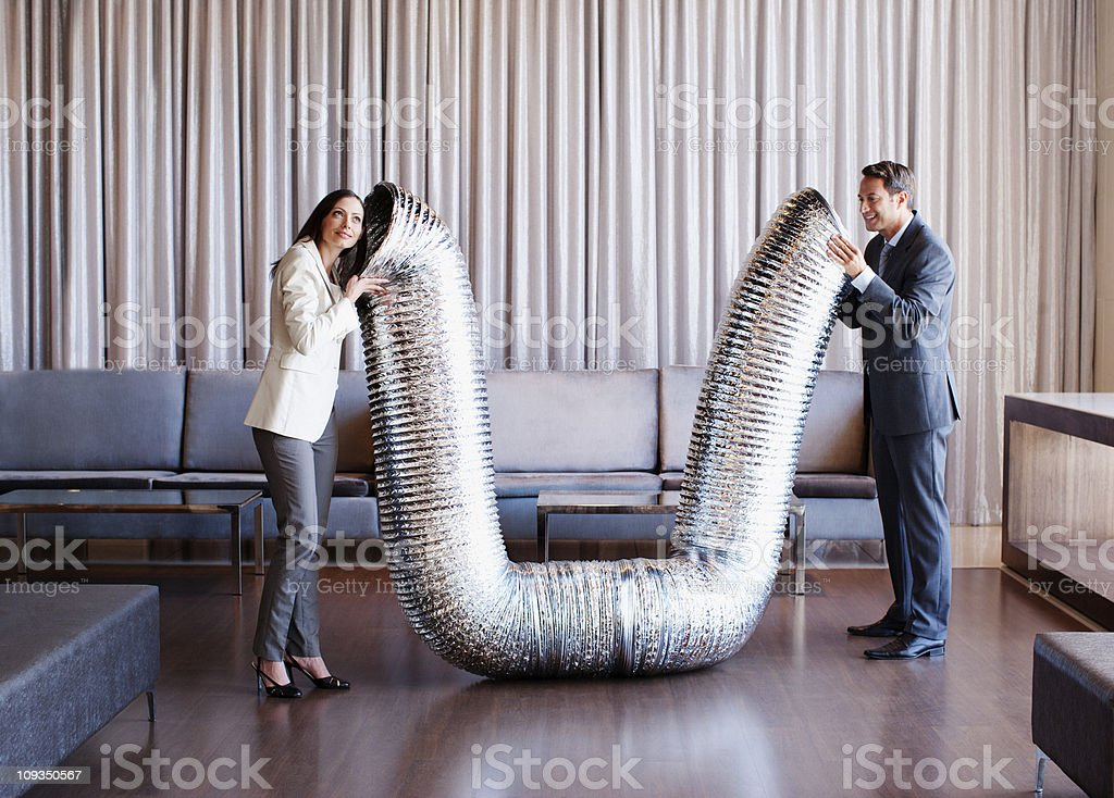 Business people holding metal tubing in hotel lobby stock photo