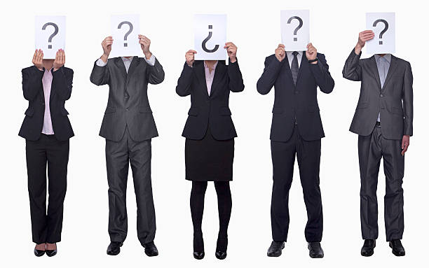 Business people holding up paper with question mark stock photo