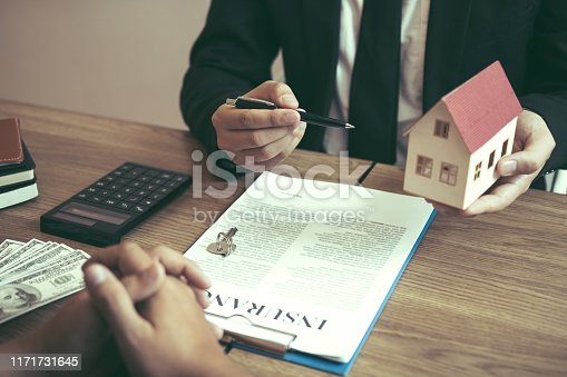 481337750istockphoto Business people home sales broker is using a pen pointing to the house model and describing the various components of the house. 1171731645