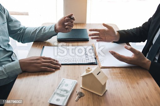 481337750 istock photo Business people home sales broker is using a pen pointing to the house model and describing the various components of the house. 1188796002