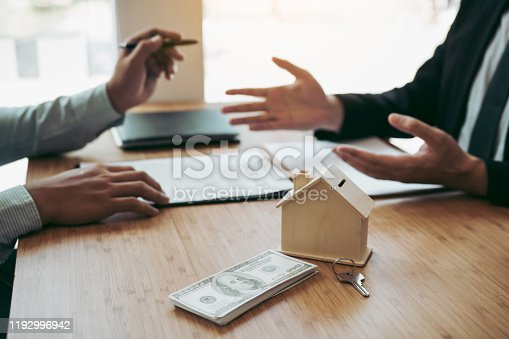 481337750 istock photo Business people home sales broker is using a pen pointing to the house model and describing the various components of the house. 1192996942