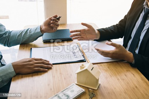 481337750 istock photo Business people home sales broker is using a pen pointing to the house model and describing the various components of the house. 1203465729