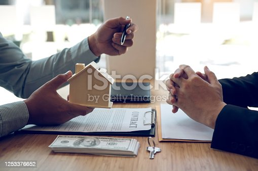 481337750 istock photo Business people home sales broker is using a pen pointing to the house model and describing the various components of the house. 1253376652