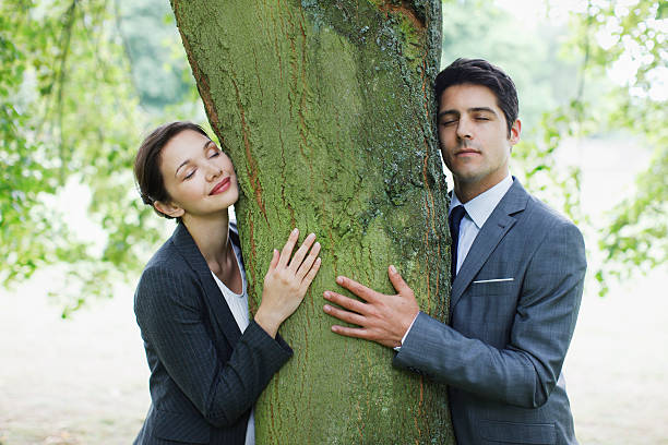 Business people hugging tree  tree hugging stock pictures, royalty-free photos & images