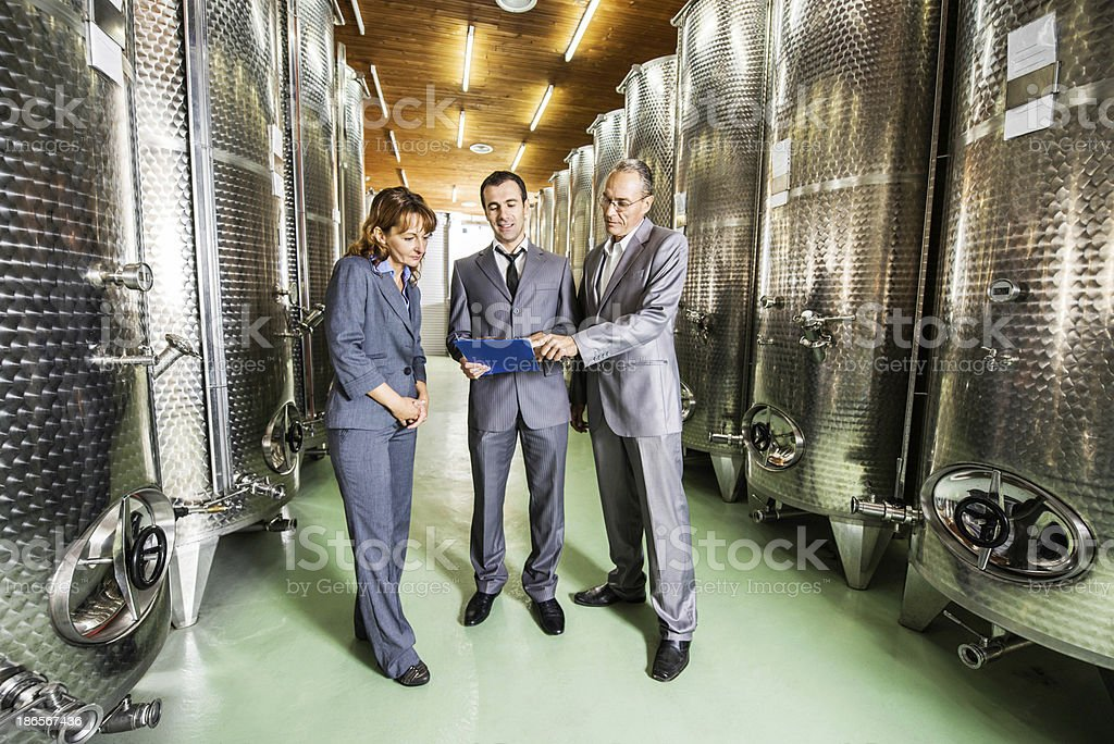 Business people in a wine cellar. royalty-free stock photo