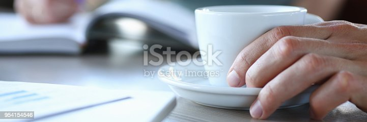business people in cafe coffee break at table hold cup of coffee in arms closeup