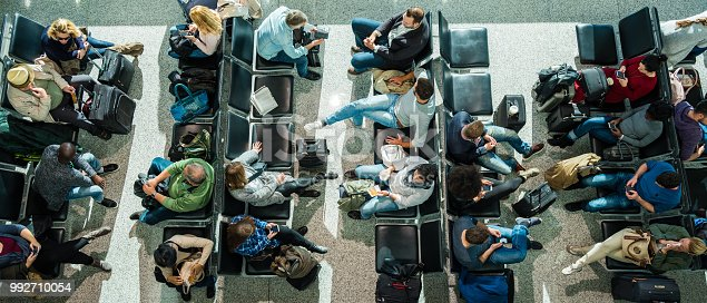 Business people waiting at airport in departure lounge.