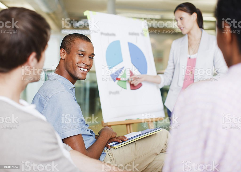 Business people in meeting looking at pie chart stock photo