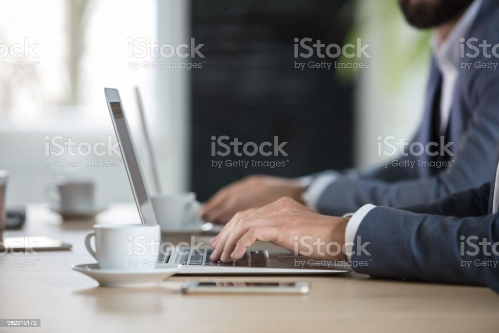 Business people in meeting room with laptop Close up of businessman sitting at conference table and using laptop with colleague in background. Adult Stock Photo
