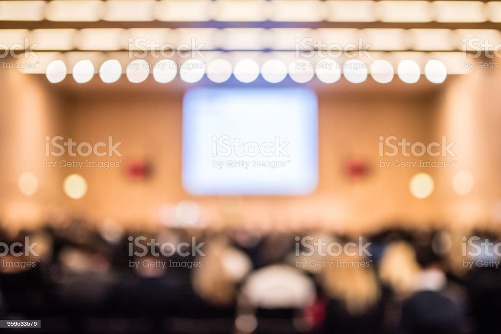 Soft focus of business people attending seminar in conference room.