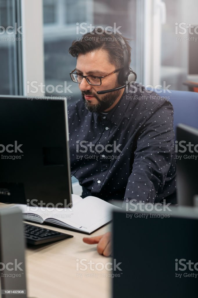 Call center worker sitting by the desk in his office and working.