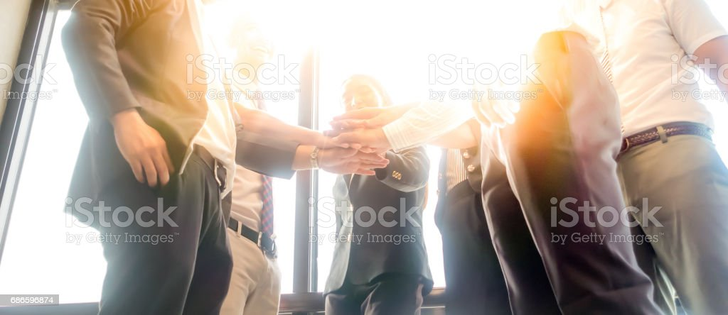 Business people join hand together during their meeting with sun rays aura background. stock photo