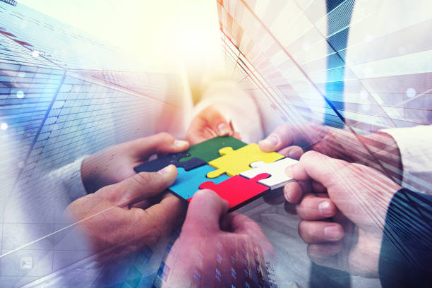 Business people join puzzle pieces in office. Concept of teamwork and partnership. double exposure with light effects - foto stock